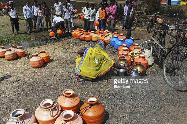 Water commuters wait in line to fill containers at a groundwater source in Latur Maharashtra India on Saturday April 16 2016 Hundreds of millions of...