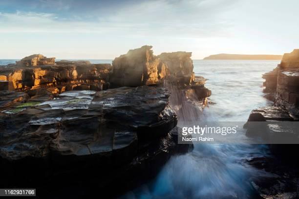 water crashing through the basalt rocks at cadillac canyon at sunset, san remo, australia - bass strait stock pictures, royalty-free photos & images