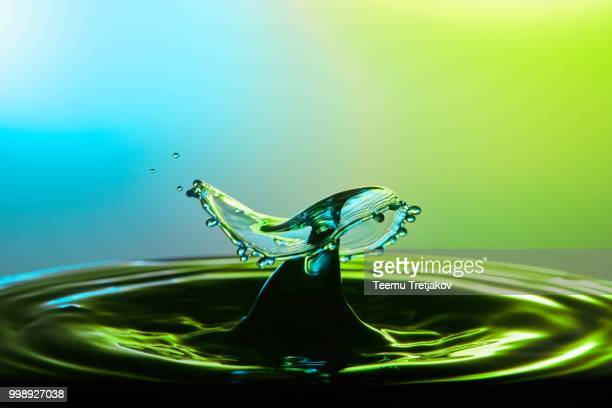 Water drop collision close up image with a green and blue background