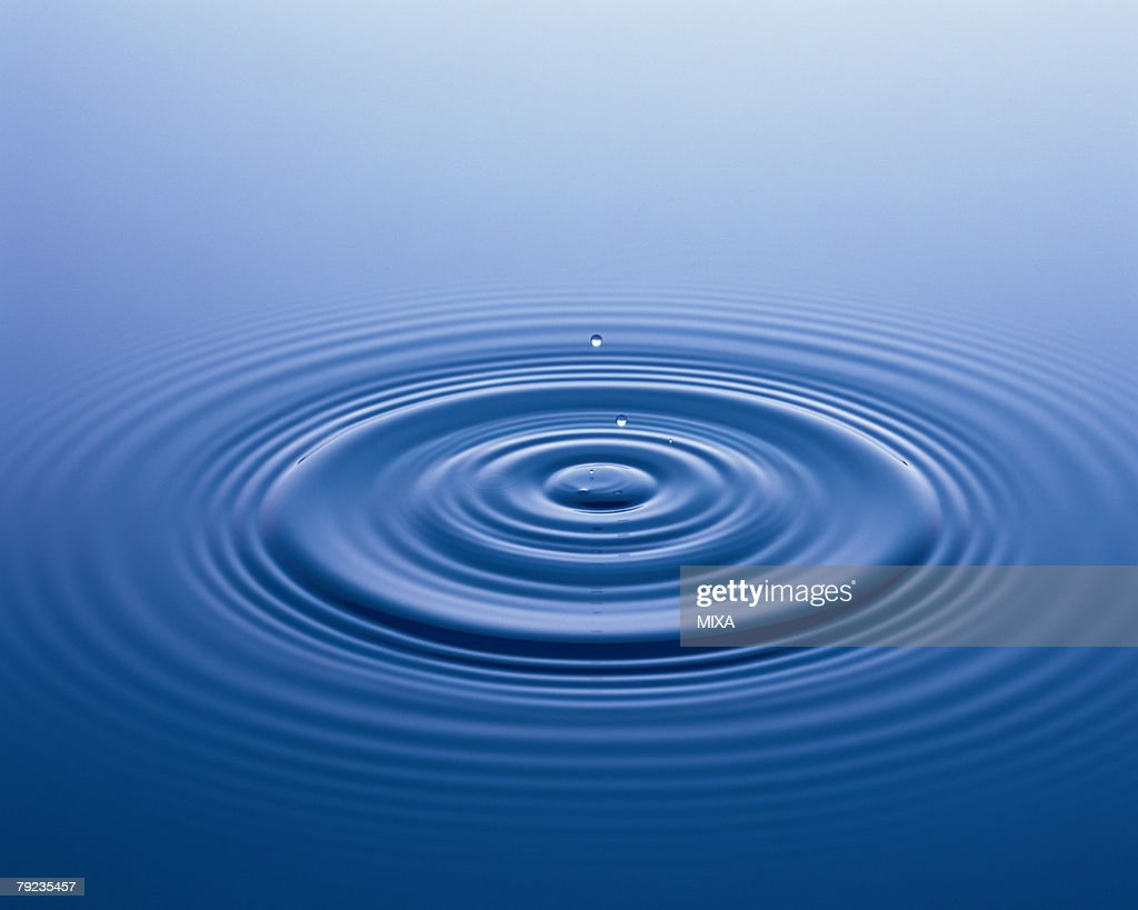 Water droplet falling on surface of water : Stock Photo