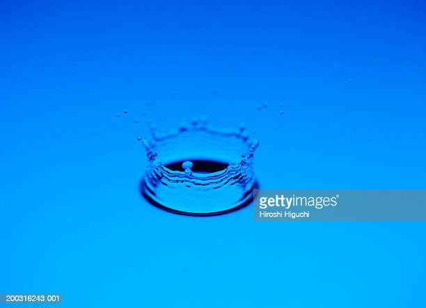 Water droplet splashing against surface of water, close-up