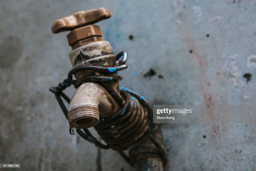 Water droplets drip from a communal tap in the Khayelitsha township, Cape Town, South Africa, on Friday, Feb. 9, 2018. Confronted by the worst drought on record after years of disastrously low rainfall, city authorities say they may have to turn off the water entirely on May 11, the famous 'Day Zero,' if reservoir levels keep falling and consumption doesn't slow enough. Photographer: Waldo Swiegers/Bloomberg via Getty Images