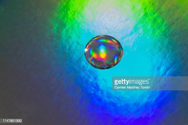 water droplets iridescent in different colors. - mercury metal stock-fotos und bilder