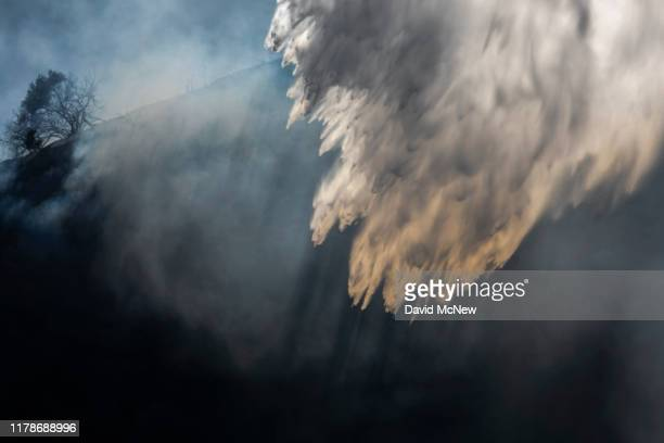 Water dropped from a firefighting helicopter falls over the Getty Fire on October 28 2019 in Los Angeles California Reported at 130 am the fire...