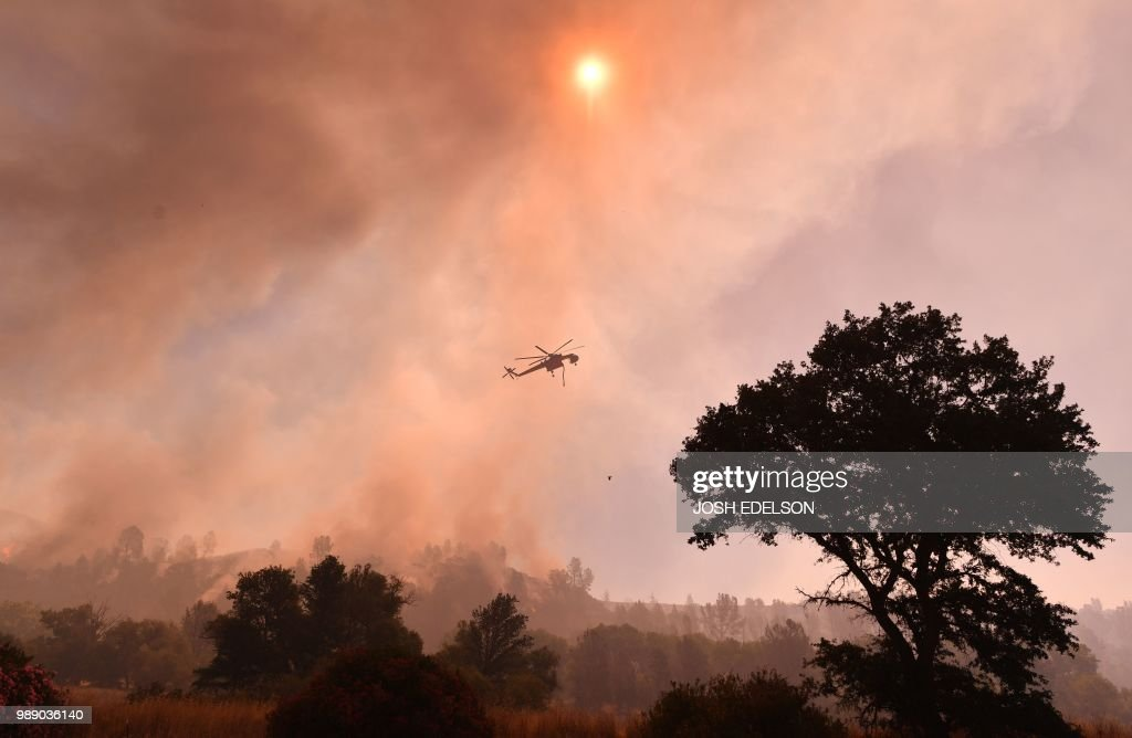A water dropping helicopter works the scene as the Pawnee fire jumps across highway 20 near Clearlake Oaks, California on July 1, 2018. - More than 30,000 acres have burned in multiple fires throughout the region.