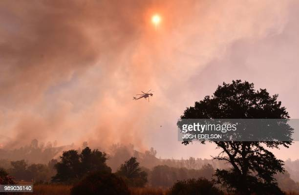 A water dropping helicopter works the scene as the Pawnee fire jumps across highway 20 near Clearlake Oaks California on July 1 2018 More than 30000...