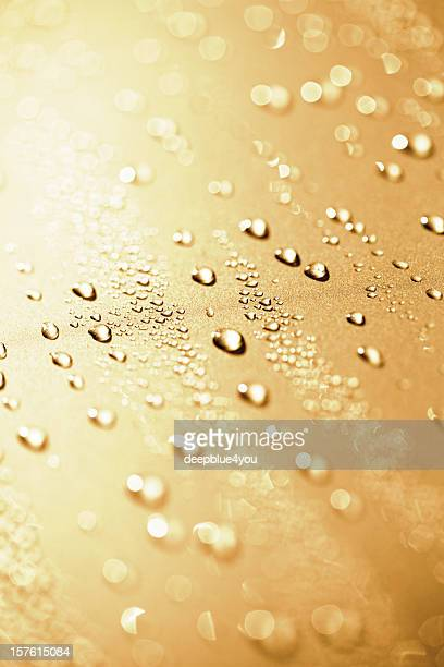 Water drops on a polished gold metalic motorhood