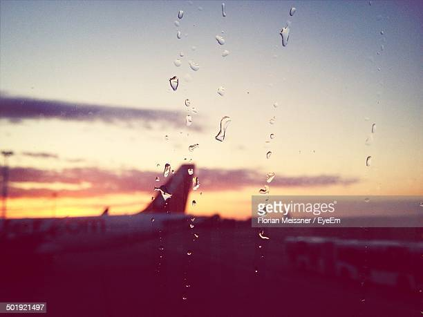 Water drops on glass with airplane at runway