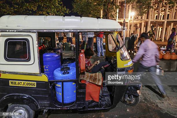 Water drums sit inside an auto rickshaw as people wait in line to fill water containers at the Vivekananda Chowk water tank in Latur Maharashtra...