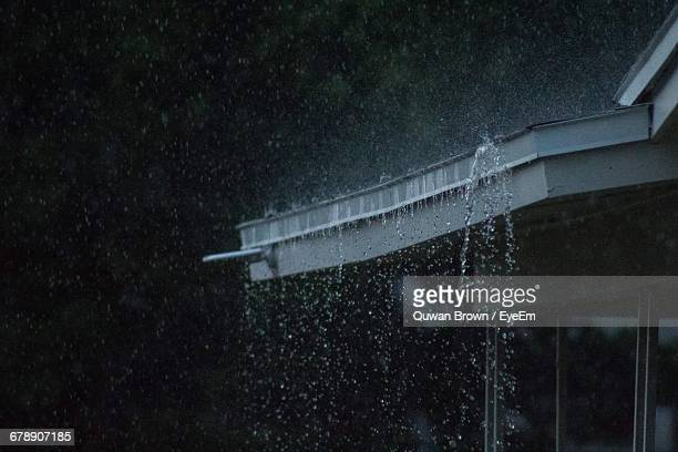 water falling from roof at night during rainy season - roof stock pictures, royalty-free photos & images