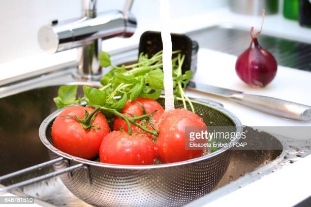 Water falling on tomatoes in colander