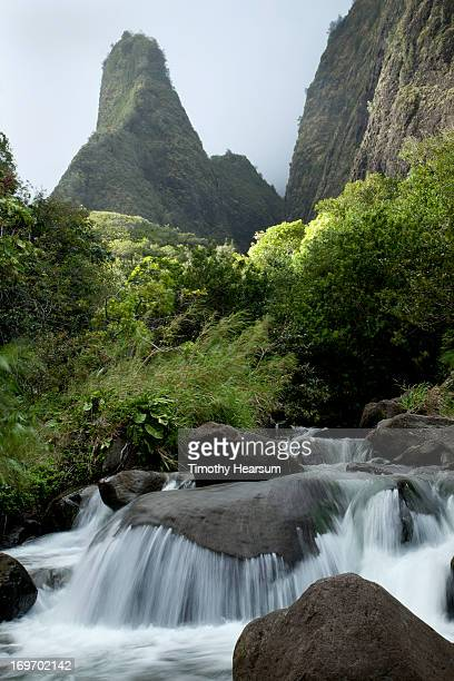 water falling over boulders; mountains beyond - timothy hearsum stock pictures, royalty-free photos & images