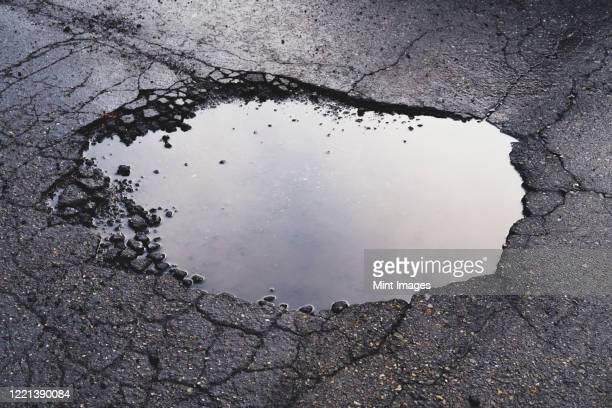 water filled pothole on urban street with cracks and fracture marks - hole stock pictures, royalty-free photos & images