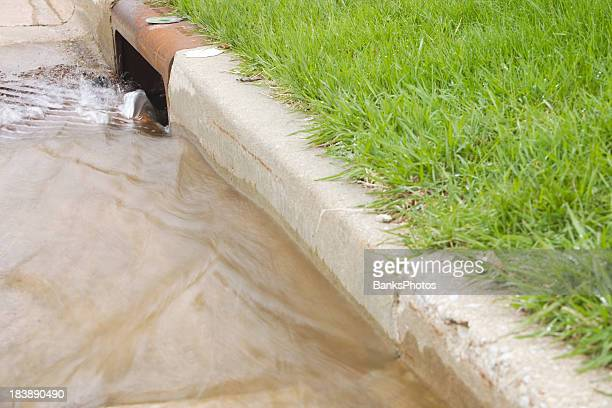 water flowing down a storm drain - sewer stock pictures, royalty-free photos & images