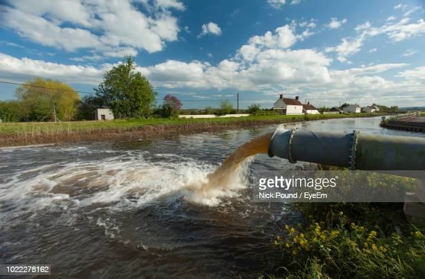 Water Flowing From Pipe Against Sky