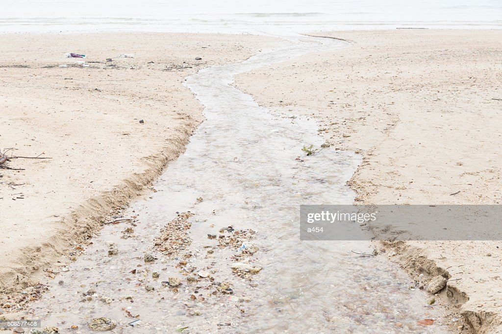 water flowing from the beach into the sea : Stock Photo
