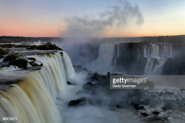 Water flowing over the Iguacu Falls leaves a cloud of mist between Brazil and Argentina as the sun sets over the Iguacu National Park on August 12...