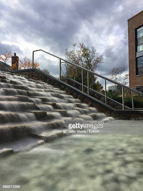 water flowing through steps against cloudy sky - bethesda maryland stock photos and pictures