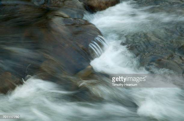 water flows over rocks in a river - timothy hearsum stock pictures, royalty-free photos & images