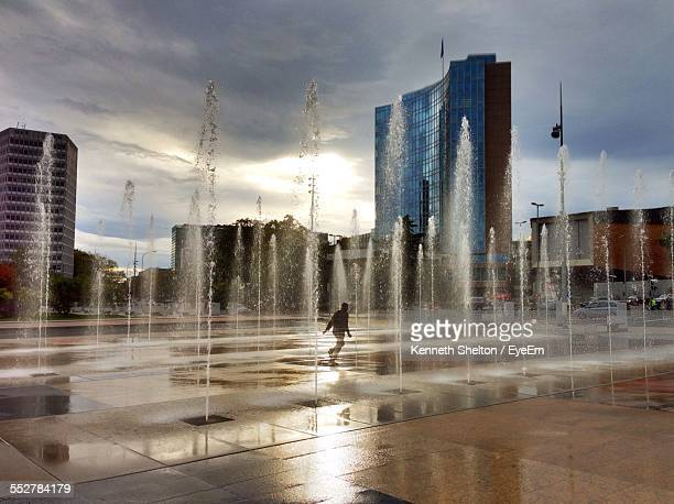 Water Fountain By City Buildings Against Cloudy Sky