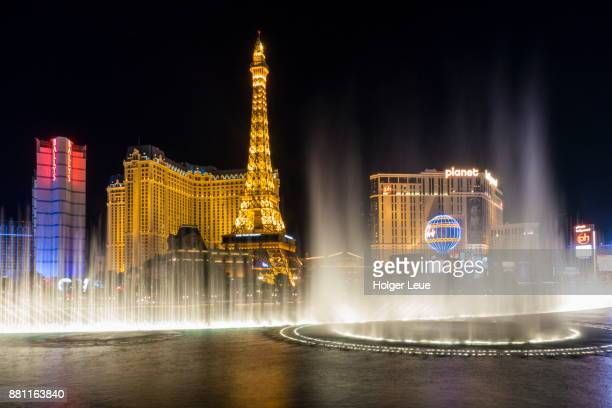 Water fountain in front of Bellagio Luxury Hotel Resort & Casino with Eiffel Tower replica of Paris Las Vegas Hotel on Las Vegas Strip at night