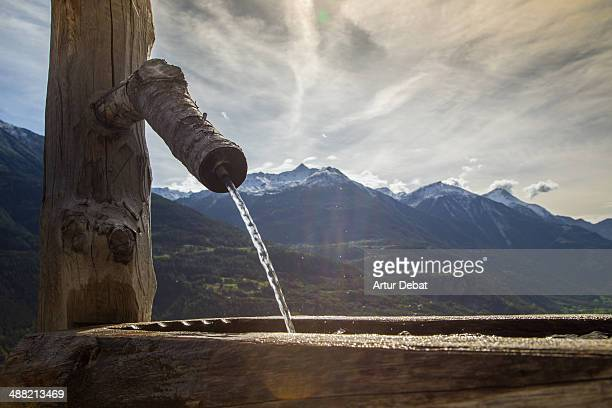 Water fountain with snowy swiss alps at summer.