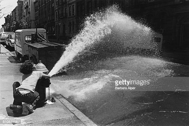 Water from a fire hydrant sprays onto a New York City street USA 12th June 1976