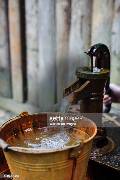 Water from water pump pouring into bucket
