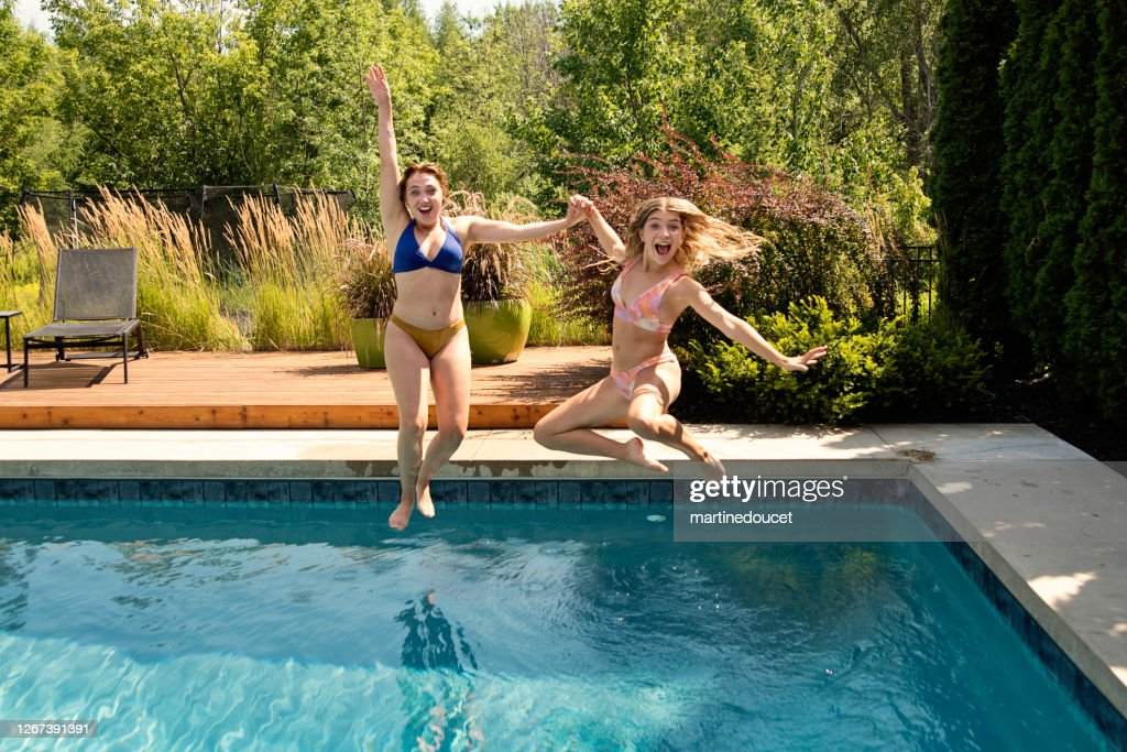 Water fun for two cousins jumping in backyard pool. : Stock Photo