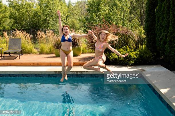 """water fun for two cousins jumping in backyard pool. - """"martine doucet"""" or martinedoucet stock pictures, royalty-free photos & images"""
