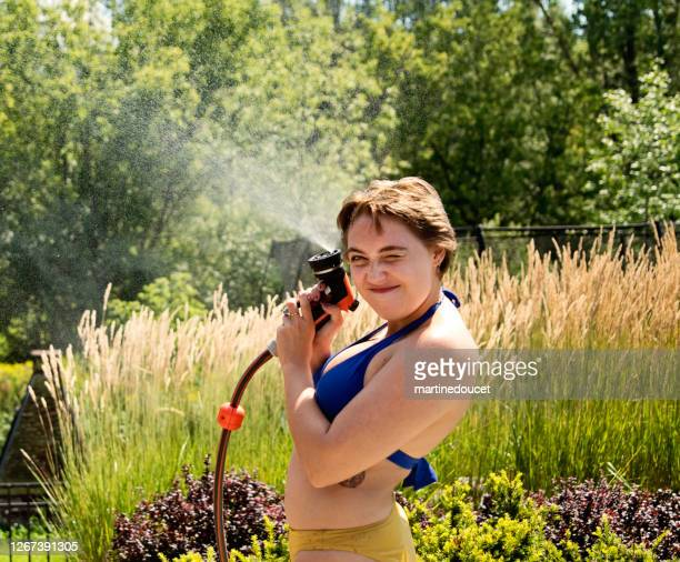 """water fun for young woman in backyard. - """"martine doucet"""" or martinedoucet stock pictures, royalty-free photos & images"""