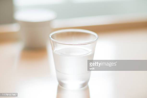 water glass on a table - ガラス ストックフォトと画像
