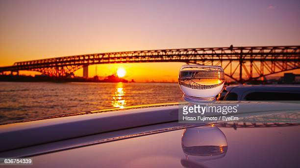 Water Glass On Car Roof Against Silhouette Bridge Over Sea During Sunset