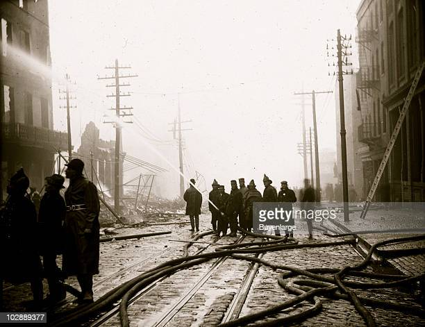 Water hoses snake along the cobbled street of Balto as firefighters train a stream of water onto the fire during the Great Baltimore Fire of 1904