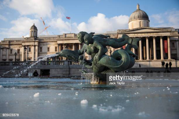 Water in a Trafalgar Square fountain is covered in a layer of ice in the freezing weather on February 28 2018 in London United Kingdom Freezing...