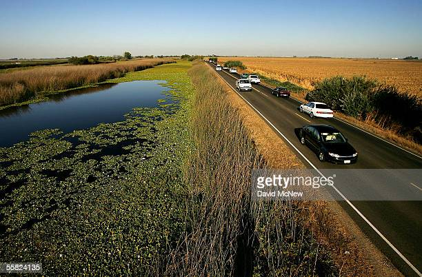 Water is held back from a lower-elevation farm by a section of Highway 4 that serves as a levee road in the Sacramento-San Joaquin River Delta, on...