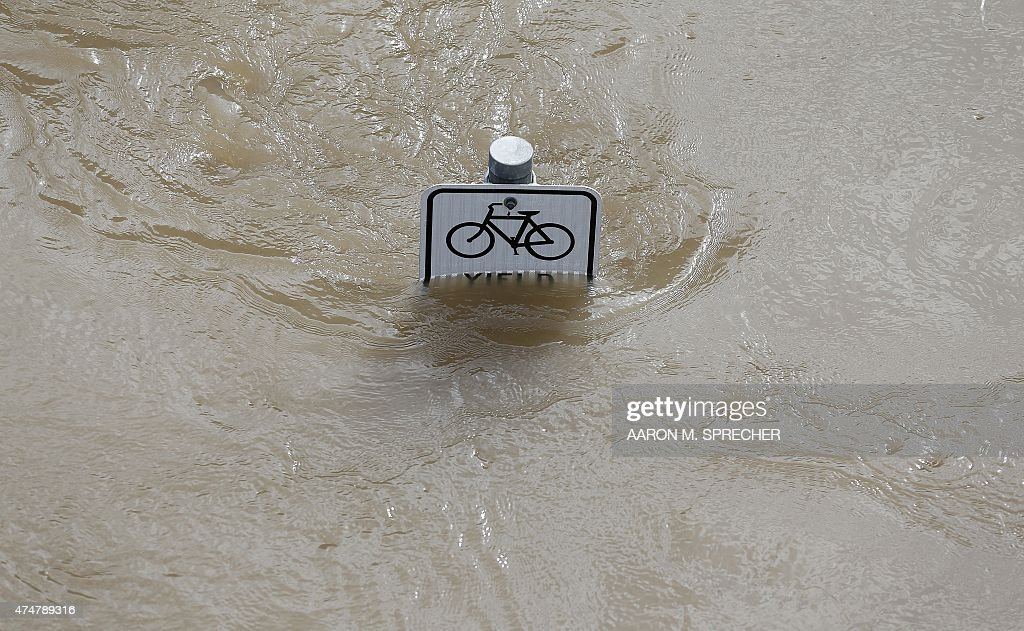 Water is seen at the top of a sign along a bike path near Memorial Drive in Houston, Texas on May 26, 2015. Heavy rains throught Texas put the city of Houston under massive amounts of water, closing roadways and trapping residents in their cars and buildings, according to local reports. Rainfall reached up to 11 inches (27.9cm) in some parts of the state, according to national forecasters, and the heavy rains quickly pooled over the state's already saturated soil.