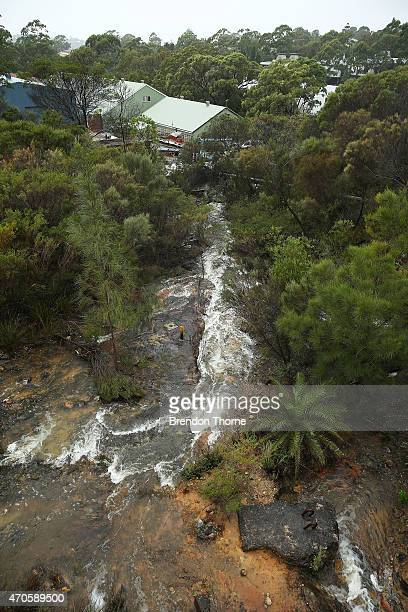 Water is seen spilling over Manly Dam and into bush land threatening local properties on April 22 2015 in Sydney Australia Three people have died and...