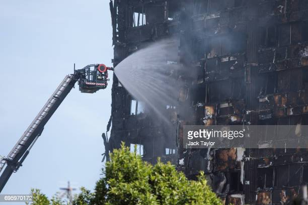 Water is sprayed by fire fighters on to the burning 24 storey residential Grenfell Tower block in Latimer Road West London on June 14 2017 in London...