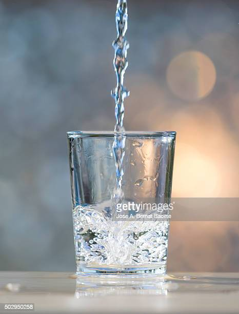 Water jet filling a glass of crystal.