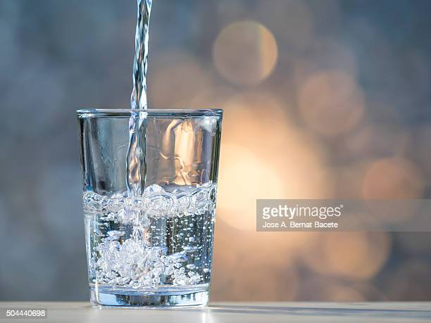 water jet filling a glass of crystal. - falling water stock photos and pictures
