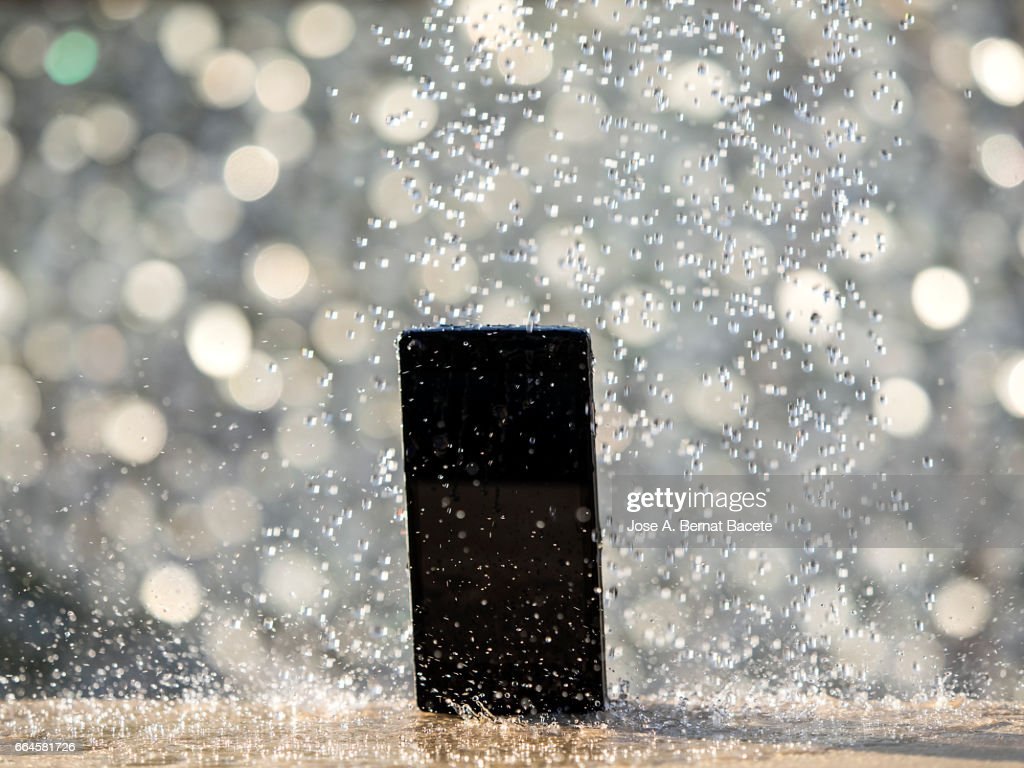 Water jet striking on a wet mobile phone, outdoors illuminated by sunlight : Stock Photo