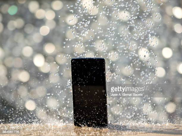 water jet striking on a wet mobile phone, outdoors illuminated by sunlight - mojado stock pictures, royalty-free photos & images