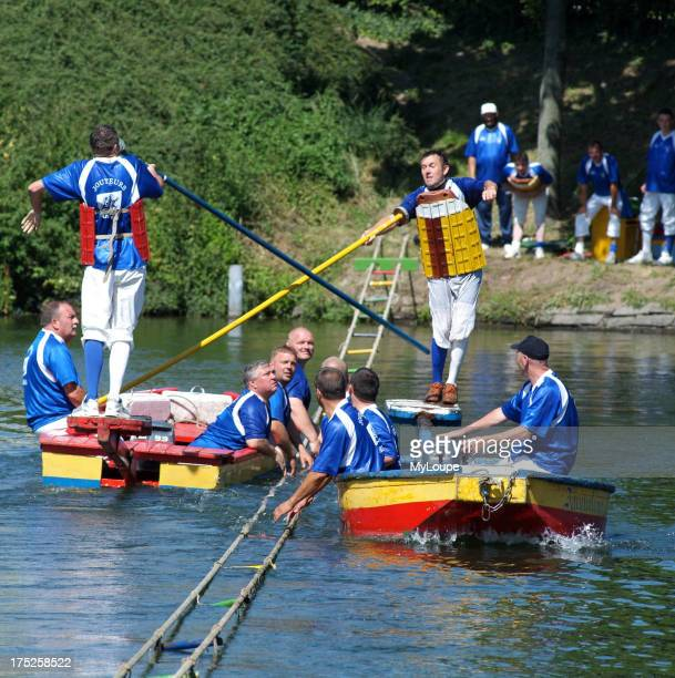 Water jousting in Arras northern France The game involves two teams in two boats one team member has a pole with which he must knock an opposing team...