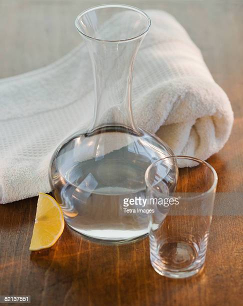 Water jug and glass next to rolled towel