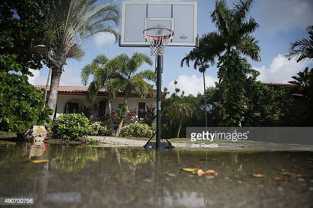 Water laps up below a basketball hoop in a flooded street caused by the combination of the lunar orbit which caused seasonal high tides and what many...
