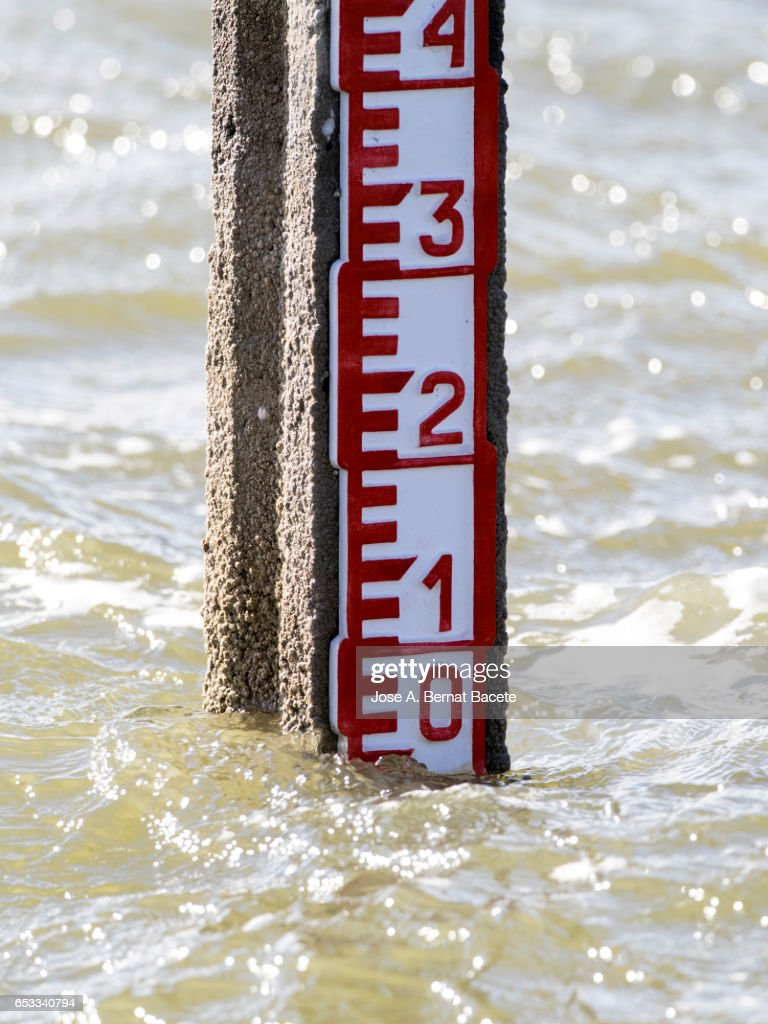 Water Level Marker in a lagoon, a wind day and with waves in the water : Stock Photo