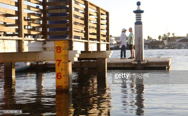 A water level marker is attached to a dock on Orange County's Balboa Island on October 20 2018 in Newport Beach California The threat of rising seas...