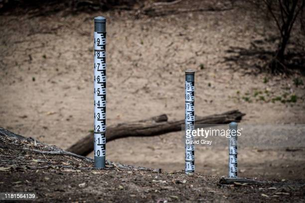 Water level markers and branches sit in the dried-up bed of the Mehi River, near the north-western New South Wales town of Collarenebri on October 7,...