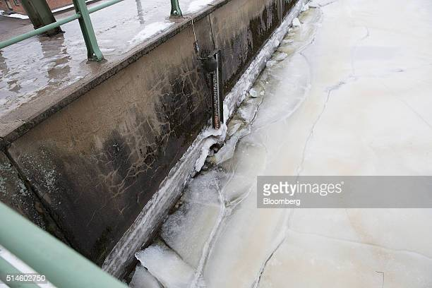 A water level meter sits surrounded by ice on a frozen river at the Ultra Hydroelectric power station operated by Fortum Oyj in Tierp Sweden on...